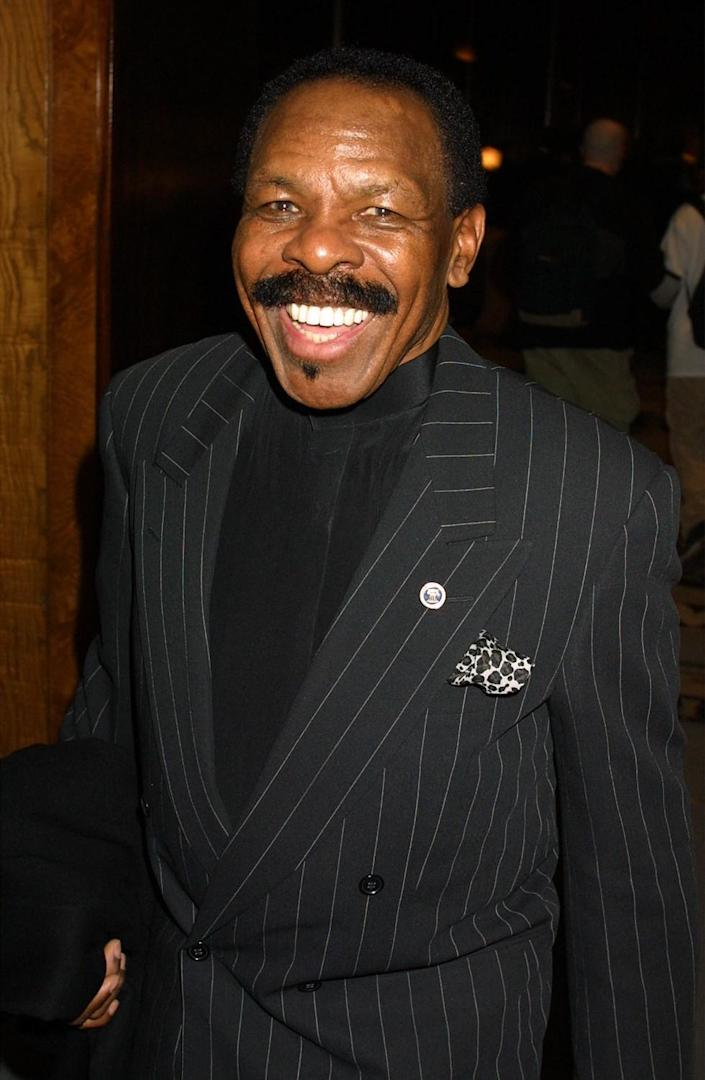 Singer Lloyd Price smiles while wearing a pinstripe jacket with a pin on his lapel.