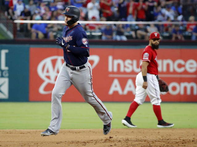 Minnesota Twins' C.J. Cron, left, rounds the bases past Texas Rangers' Rougned Odor after hitting a two-run home run during the first inning of a baseball game in Arlington, Texas, Saturday, Aug. 17, 2019. The shot scored Marwin Gonzalez. (AP Photo/Tony Gutierrez)