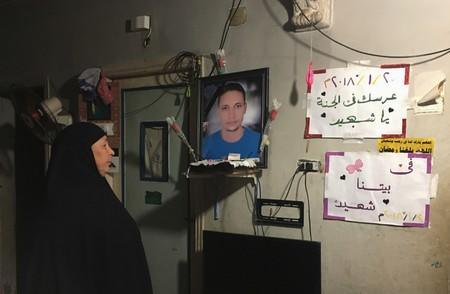 Lotfy Ibrahim's mother Tahany looks at a photograph of her son at home in Kafr al-Sheikh