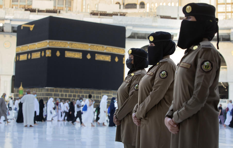 In this July 20, 2021 photo, Saudi police women, who were recently deployed to the service, from right to left, Samar, Alaa, and Bashair, stand alert in front of the Kaaba, the cubic building at the Grand Mosque, during the annual hajj pilgrimage in the Saudi Arabia's holy city of Mecca. The cloud of social restrictions that loomed over generations of Saudis is quickly dissipating and the country is undergoing visible change. Still, for countless numbers of people in the United States and beyond, Saudi Arabia will forever be associated with 9/11. (AP Photo/Amr Nabil)
