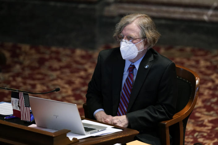 State Sen. Herman Quirmbach, D-Ames, works at his desk in the Iowa Senate chamber, Wednesday, Feb. 24, 2021, at the Statehouse in Des Moines, Iowa. Iowa Republicans were moving swiftly Wednesday to sharply limit early voting in the state, months after a general election overseen by a Republican secretary of state resulted in record turnout and overwhelming victories by GOP candidates. (AP Photo/Charlie Neibergall)