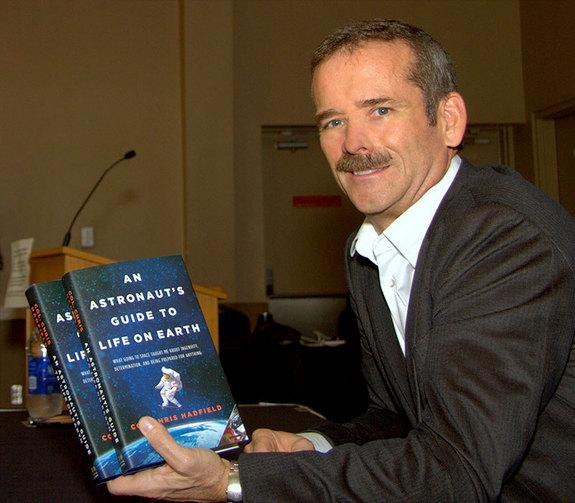 "Canadian astronaut Chris Hadfield holds up copies of his book, ""An Astronaut's Guide to Life on Earth."""