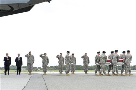 Defense Secretary Chuck Hagel and Secretary of the Army John McHugh salute as a U.S. Army carry team transfers the remains of Army Pfc. Cody J. Patterson of Philomath, Oregon at Dover Air Force Base
