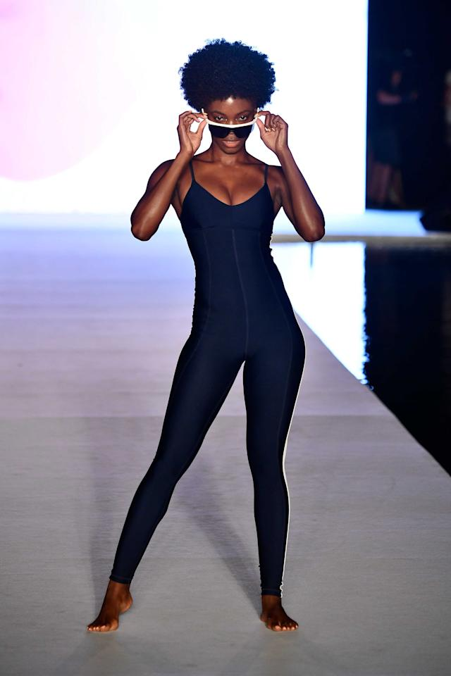 <p>A model walks the runway wearing a sporty catsuit and shades for the runway show during the Paraiso Fashion Fair in Miami at the W South Beach hotel on July 15. (Photo: Alexander Tamargo/Getty Images for Sports Illustrated) </p>