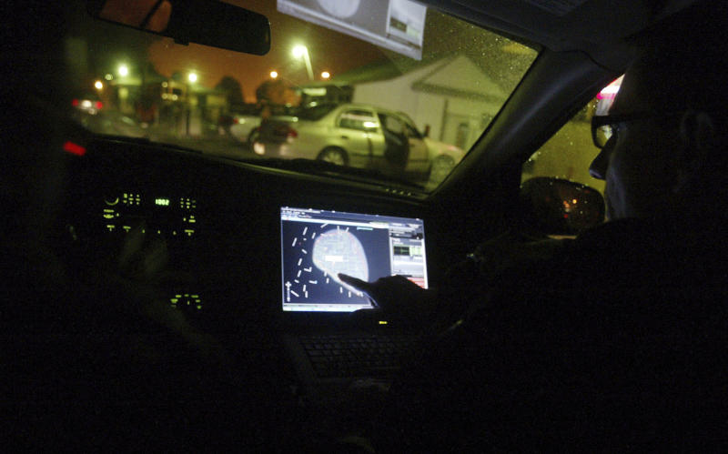 FILE - In this Dec. 31, 2008 file photo, engineer Stephan Noetzel alerts a police officer to gunshots using ShotSpotter, strategically placed acoustic sensors designed to help police track gunfire in East Palo Alto, Calif. A gunman on the loose in downtown Fresno was intent on killing as many white people as he could, taking down three people in just a few minutes Tuesday, April 18, 2017. Police Chief Jerry Dyer credits the technology that detects the sound of gunshots with allowing police to apprehend the gunman Kori Ali Muhammad just 4 minutes after his shooting rampage began, limiting the carnage to four people in all. (AP Photo/Mathew Sumner, File)