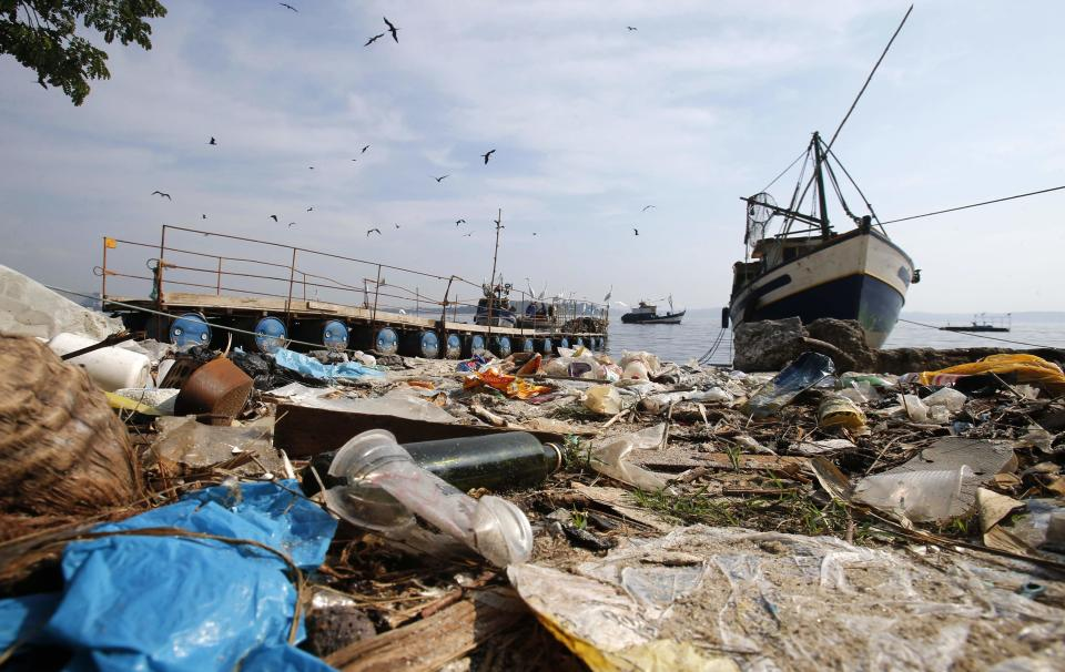 Garbage is seen near a fishing boat on Fundao beach in the Guanabara Bay in Rio de Janeiro March 13, 2014. REUTERS/Sergio Moraes