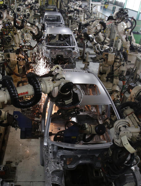 Robots work on the assembly line of the Mazda6 (Atenza) model at Mazda Motor Corp.'s plant in Hofu, Yamaguchi prefecture, southwestern Japan, Tuesday, Aug. 27, 2013. Mazda, the longtime also-ran of Japanese automakers, shows a new super-efficient plant that's rolling off vehicles at a stunning rate of one every 54 seconds. The plant is part of the reason why Mazda has managed to defy skeptics who've predicted fates ranging from bankruptcy to a buyout by Chinese interests. (AP Photo/Shizuo Kambayashi)