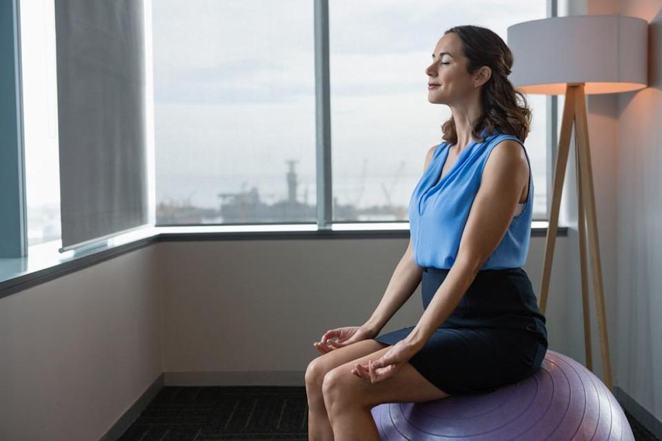 """Make your workday healthier and more enjoyable by subbing in an exercise ball for that traditional desk chair. In addition to making those hours stuck behind your desk a little more fun, a 2013 study published in <em>BioMed Research International</em> showed that students whose chairs were replaced with exercise balls had <a href=""""https://www.ncbi.nlm.nih.gov/pmc/articles/PMC3691892/"""" rel=""""nofollow noopener"""" target=""""_blank"""" data-ylk=""""slk:less physical discomfort"""" class=""""link rapid-noclick-resp"""">less physical discomfort</a> and greater academic performance."""
