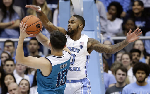 North Carolina's Seventh Woods (0) blocks UNC Wilmington's Kai Toews (10) during the first half of an NCAA college basketball game in Chapel Hill, N.C., Wednesday, Dec. 5, 2018. (AP Photo/Gerry Broome)