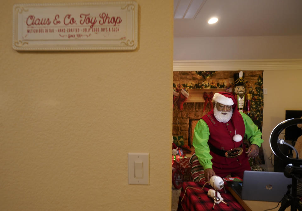 Larry Jefferson prepares to portray Santa Claus for virtual visits with kids from his home in Duncanville, Texas, on Dec. 9, 2020. In this socially distant holiday season, Santa Claus is still coming to towns (and shopping malls) across America but with a few 2020 rules in effect. (AP Photo/LM Otero)