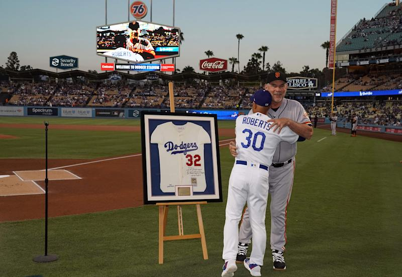 Sep 6, 2019; Los Angeles, CA, USA; Los Angeles Dodgers manager Dave Roberts (30) presents retiring San Francisco Giants manager Bruce Bochy (15) an autographed Sandy Koufax jersey before a game at Dodger Stadium. Mandatory Credit: Kirby Lee-USA TODAY Sports