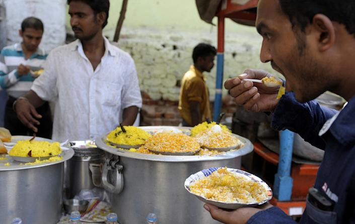 Indian customers eat egg rice at a roadside stall in Hyderabad on June 3, 2013 (AFP Photo/Noah Seelam)