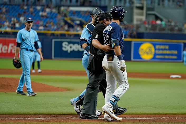 Rays outfielder Kevin Kiermaier is held back by home plate umpire Bruce Dreckman after he was hit by a pitch from Blue Jays pitcher Ryan Borucki, left, in their game on Wednesday.