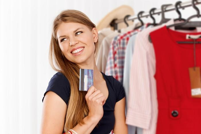A smiling young woman holding a credit card while next to a retail clothing rack.