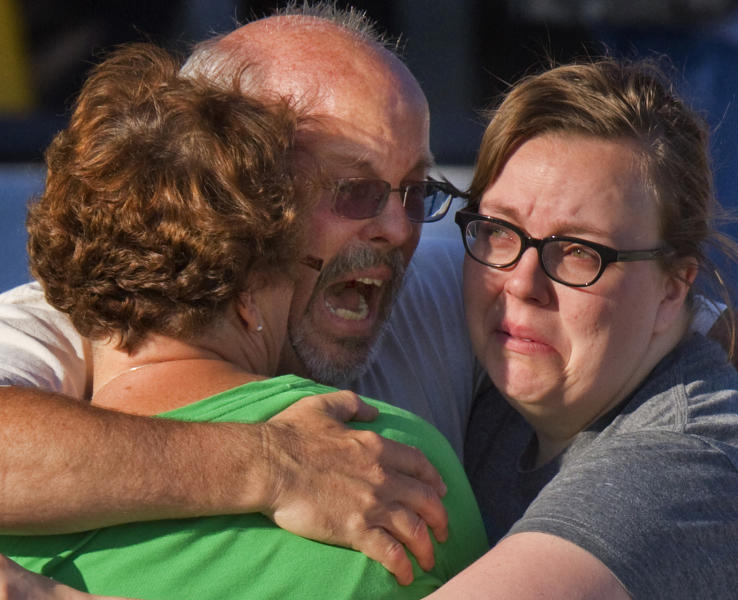 """Tom Sullivan, center, embraces family members outside Gateway High School where he has been searching franticly for his son Alex Sullivan who celebrated his 27th birthday by going to see """"The Dark Knight Rises,"""" movie where a gunman opened fire Friday, July 20, 2012, in Aurora, Colo. (AP Photo/Barry Gutierrez)"""
