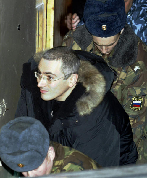 FILE In this Tuesday, Dec. 23, 2003 file photo Mikhail Khodorkovsky, former chief of Russia's largest oil company, Yukos, center, is escorted by police officers as he leaves a court in Moscow, Russia. Russian President Vladimir Putin said on Thursday Dec. 19, 2013, that he will pardon his arch-enemy Khodorkovsky who has spent the past 10 years in prison on tax evasion and embezzlement charges. Khodorkovsky's release could potentially be Putin's biggest political decision this year. (AP Photo/Sergey Ponomarev, File)