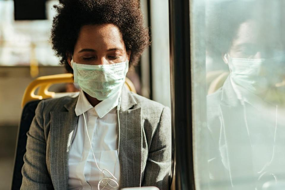 woman with protective mask on her face commuting by bus during virus epidemic.