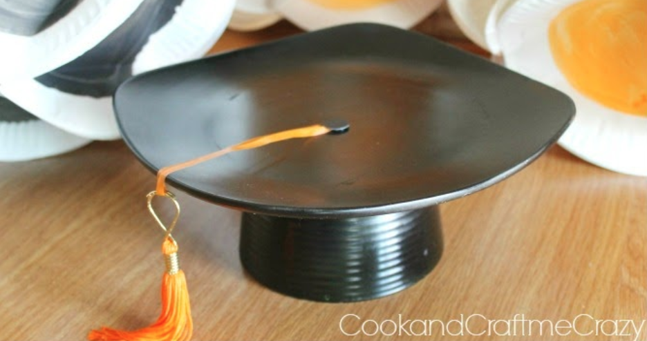 """<p>Instead of displaying all your snacks on regular stands and plates, consider putting together one of these grad cap centerpieces. It's an easy DIY that will make a big statement.</p><p><strong>See the tutorial at </strong><a href=""""http://cookandcraftmecrazy.blogspot.com/2014/04/graduation-cap-centerpieces.html"""" rel=""""nofollow noopener"""" target=""""_blank"""" data-ylk=""""slk:Cook and Craft Me Crazy"""" class=""""link rapid-noclick-resp""""><strong>Cook and Craft Me Crazy</strong></a><strong>.</strong></p><p><a class=""""link rapid-noclick-resp"""" href=""""https://www.amazon.com/10-Strawberry-Street-6SQ-12ACE-BB-Appetizer/dp/B00KGGSOGU/?tag=syn-yahoo-20&ascsubtag=%5Bartid%7C10050.g.31121022%5Bsrc%7Cyahoo-us"""" rel=""""nofollow noopener"""" target=""""_blank"""" data-ylk=""""slk:SHOP PLATES""""><strong>SHOP PLATES</strong></a></p>"""