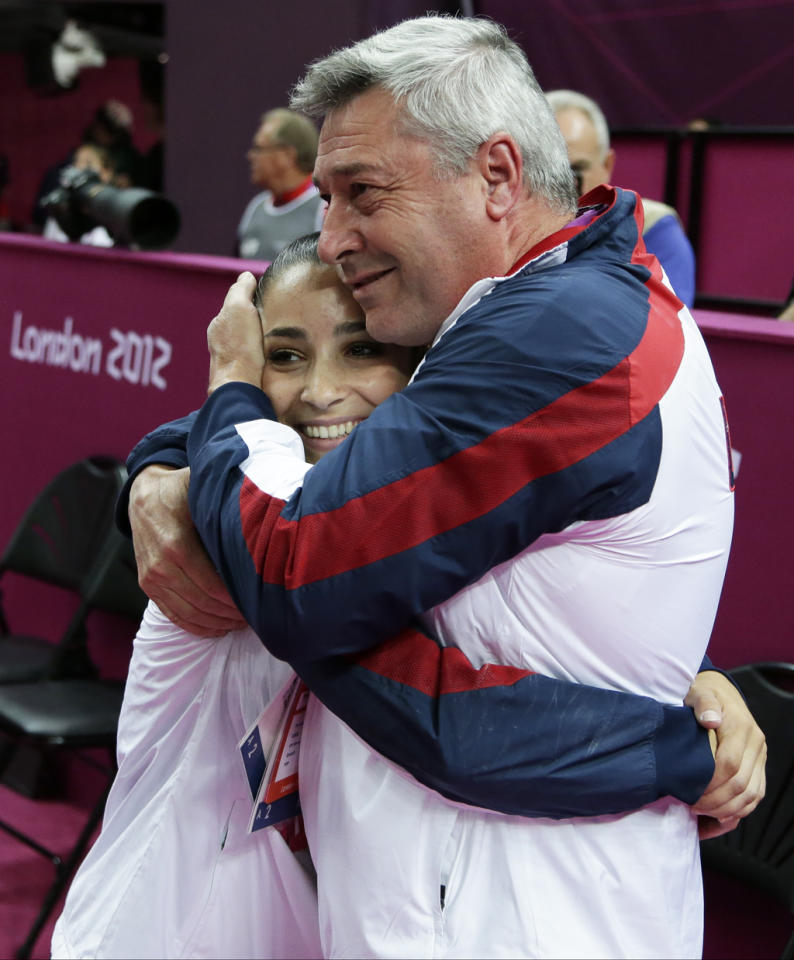 U.S. gymnast Alexandra Raisman hugs coach Mihai Brestyan after results were amended and she was declared winner of the bronze medal during the artistic gymnastics women's apparatus finals for the beam at the 2012 Summer Olympics, Tuesday, Aug. 7, 2012, in London. (AP Photo/Gregory Bull)