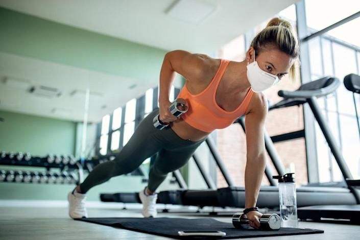 Female athlete with protective face mask doing plank exercise with hand weights in a gym.
