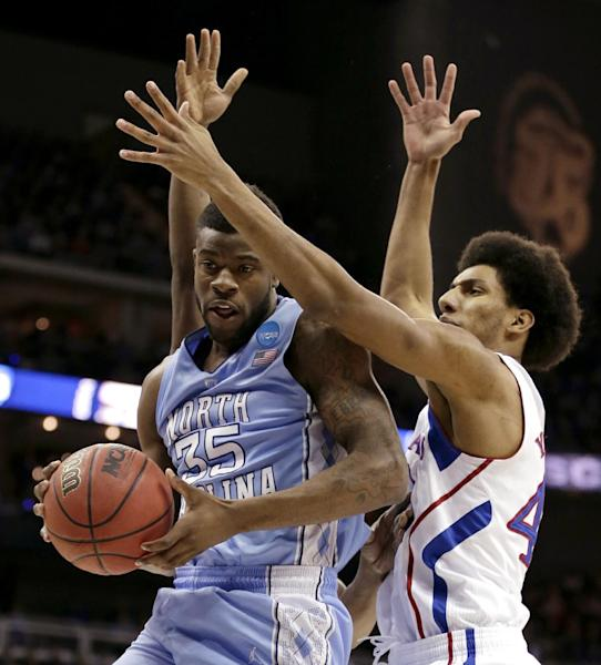 North Carolina guard Reggie Bullock (35) is pressured by Kansas forward Kevin Young (40) during the first half of a third-round game in the NCAA college basketball tournament Sunday, March 24, 2013, in Kansas City, Mo. (AP Photo/Charlie Riedel)