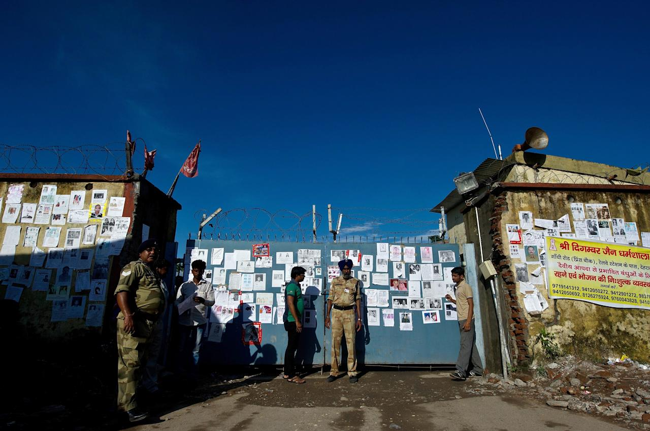 Indian security personnel stand guard at an entrance gate - seen covered with portraits of missing pilgrims - of the Jolly Grant Airport in Dehradun, state capital of Uttarakhand, on June 26, 2013. Around 1,000 people have been killed in flash floods and landslides in northern India, as a top official warned June 24 that rebuilding of the devastated Himalayan region would take years.  AFP PHOTO/MANAN VATSYAYANA