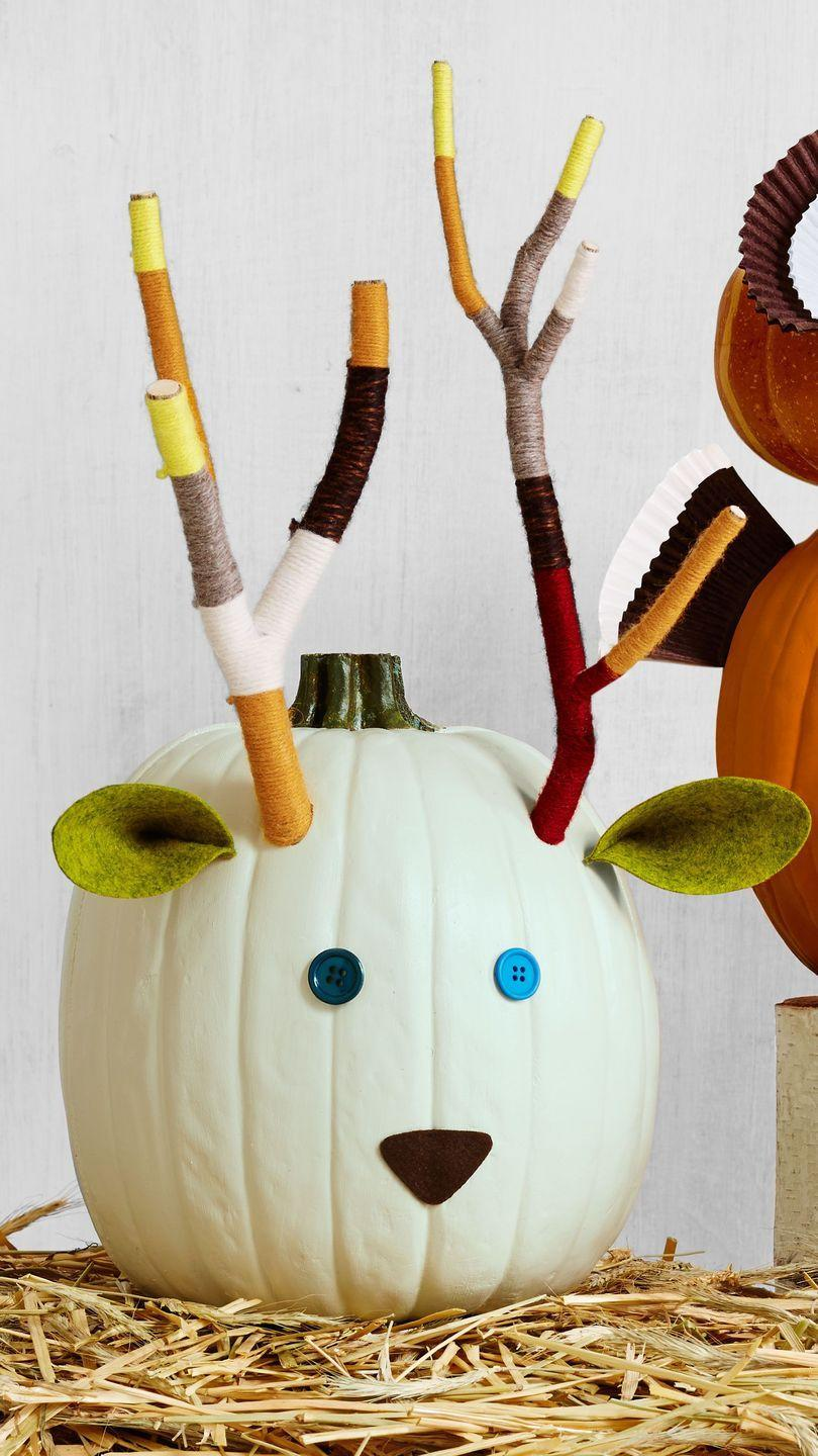 <p>Thanks to yarn-wrapped tree branches, this woodland decoration looks just like the real deal. <strong><br></strong></p><p><strong>Make the pumpkin:</strong> Use a plain white pumpkin (like Lumina) as the base. Assemble tree branches and tightly wrap assorted colors of yarn in color block patterns. Secure loose yarn ends with hot-glue. To attach the antlers, drill two holes into the upper third of the pumpkin, keeping the drill bit angled down so antlers stick up, not out. Attach button eyes, a triangle felt nose, and pinched felt triangle ears with hot-glue. </p>