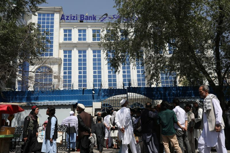 Afghans wait in line in front of Azizi Bank in Kabul