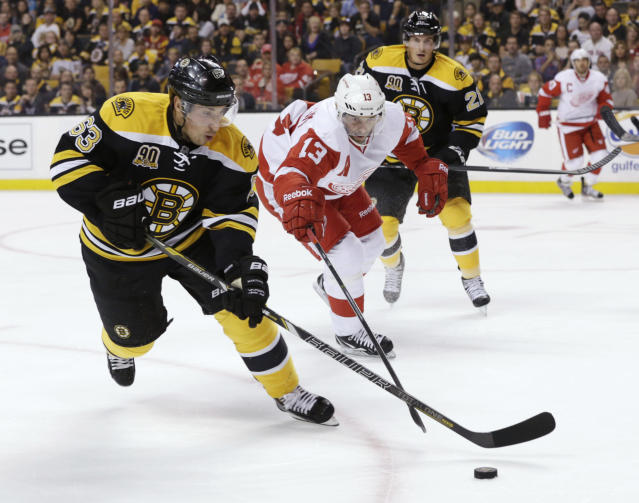 Boston Bruins forward Brad Marchand (63) and Detroit Red Wings' Pavel Datsyuk (13), of Russia, chase the puck during the first period of an NHL hockey game on Saturday Oct. 5, 2013, in Boston. (AP Photo/Robert F. Bukaty)