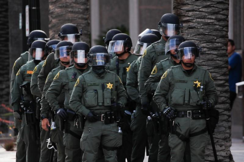 Law enforcement officers stand guard as demonstrators take part in a demonstration against the death in Minneapolis police custody of George Floyd, in Anaheim