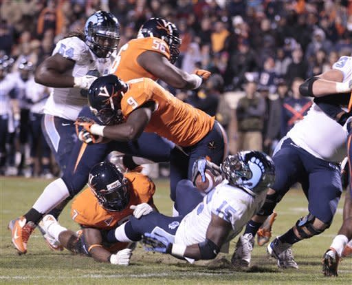 North Carolina running back A.J. Blue (15) backs in for a touchdown as Virginia defensive end Eli Harold (7) and linebacker LaRoy Reynolds (9) try to make the stop during the first half of an NCAA college football game at Scott stadium Thursday, Nov. 15, 2012 in Charlottesville, VA (AP Photo/Steve Helber)