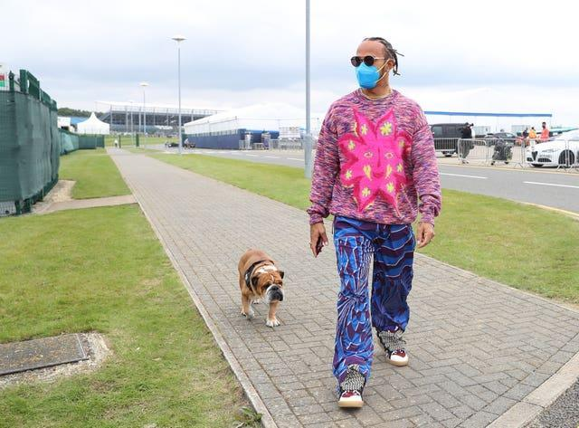 Lewis Hamilton and his dog Roscoe arrive at the paddock at Silverstone