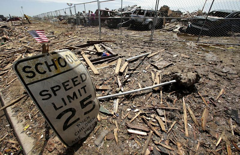 A battered sign stands outside the wreckage of Plaza Towers Elementary School, where seven children were killed earlier in the week when a tornado hit Moore, Okla., Thursday, May 23, 2013. Cleanup continues three days after a huge tornado roared through the Oklahoma City suburb, flattening a wide swath of homes and businesses. (AP Photo/Charlie Riedel)