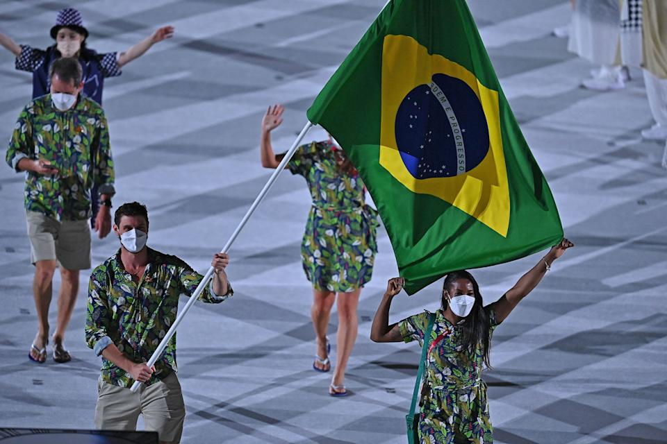 <p>Brazil's flag bearer Bruno Mossa Rezende and Brazil's flag bearer Ketleyn Quadros delegation parade during the opening ceremony of the Tokyo 2020 Olympic Games, at the Olympic Stadium, in Tokyo, on July 23, 2021. (Photo by Ben STANSALL / AFP) (Photo by BEN STANSALL/AFP via Getty Images)</p>