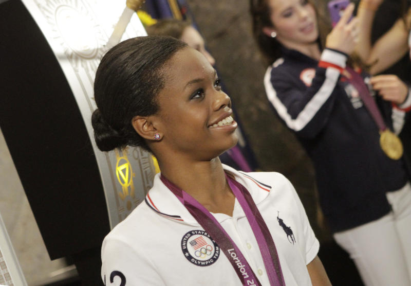 U.S. Women's Gymnastics Olympic team gold-medal winner Gabby Douglas poses with team members at the Empire State Building, Tuesday, Aug. 14, 2012 in New York. (AP Photo/Alex Katz)