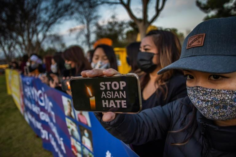 Julie Tran holds her phone during a candlelight vigil in Garden Grove, California