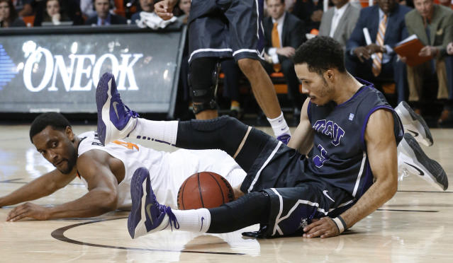 TCU guard Kyan Anderson (5) and Oklahoma State wing Brian Williams (4) watch the ball after Anderson knocked it away from Williams during the second half of an NCAA college basketball game in Stillwater, Okla., Wednesday, Jan. 15, 2014. Oklahoma State won 82-50. (AP Photo/Sue Ogrocki)