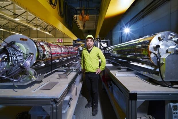 Makoto Fujiwara stands in front of ALPHA experiment apparatus at the European Organization for Nuclear Research (CERN) in Switzerland. The international collaboration equipped the apparatus with the special laser to slow down and cool antimatter atoms of hydrogen.