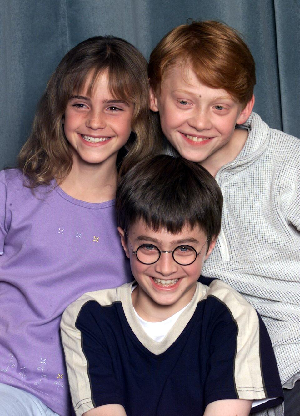 "LONDON - AUGUST 23: Actors Emma Watson (L), Daniel Radcliffe (C) and Rupert Grint (R) attend a press conference for the movie ""Harry Potter and The Philosopher's Stone"" in London on August 23, 2000. They are to play the main characters of Hermione Granger, Harry Potter and Ron Weasley in the film of the popular book by JK Rowling. (Photo by Dave Hogan/Getty Images)"