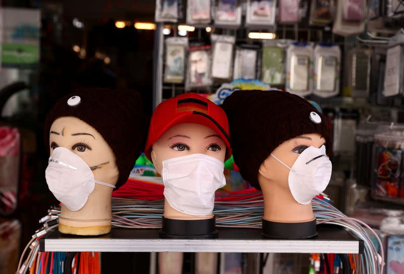 Protective masks for the coronavirus disease ( COVID-19 ) are on display for sale at a mobile phone accessory shop in Hanau
