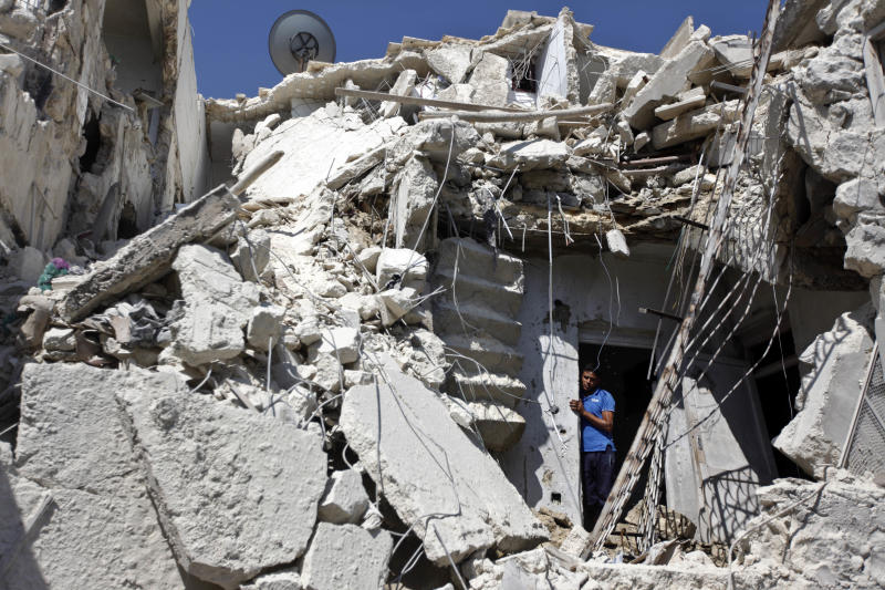 FILE - In this Sunday, Aug. 19, 2012 file photo, a Syrian man looks out of the rubble as rescuers, not shown, look for the bodies of two girls thought to be under the rubble of a building hit by a Syrian government airstrike in Aleppo, Syria. Its forces stretched thin on multiple fronts, President Bashar Assad's regime has significantly increased its use of air power against Syrian rebels in recent weeks, causing mounting civilian casualties. The shift is providing useful clues about the capability of the air force as Western powers consider the option of enforcing a no-fly zone over the northern part of the country.(AP Photo/ Khalil Hamra, File)