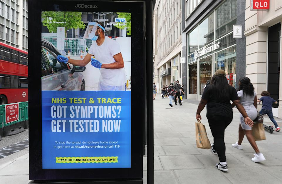 Shoppers walk past a screen on a bus stop displaying a NHS notice on test and trace on Oxford Street, London, as non-essential shops in England open their doors to customers for the first time since coronavirus lockdown restrictions were imposed in March. Picture date: Monday June 15, 2020.