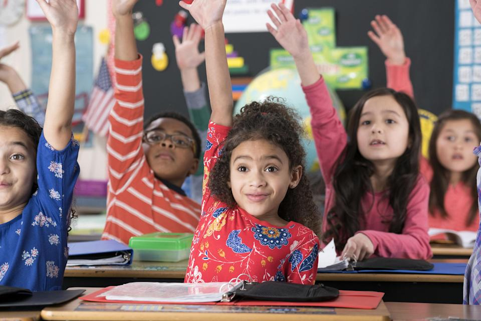 Young students eagerly raise their hands high in a classroom