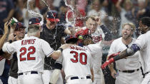 The Cleveland Indians mob Carlos Santana after Santana hit a game-winning solo home run in the ninth inning of a baseball game against the Boston Red Sox, Monday, Aug. 12, 2019, in Cleveland. The Indians won 6-5. (AP Photo/Tony Dejak)