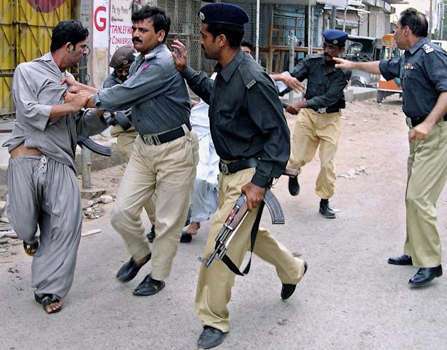 <p>Pakistani police officers detain the supporters of ethnic-Baluch tribal chief Nawab Akbar Bugti, who trying to hold a protest after the killing of their leader, Aug. 27, 2006 in Karachi, Pakistan. (AP Photo/Shakil Adil) </p>