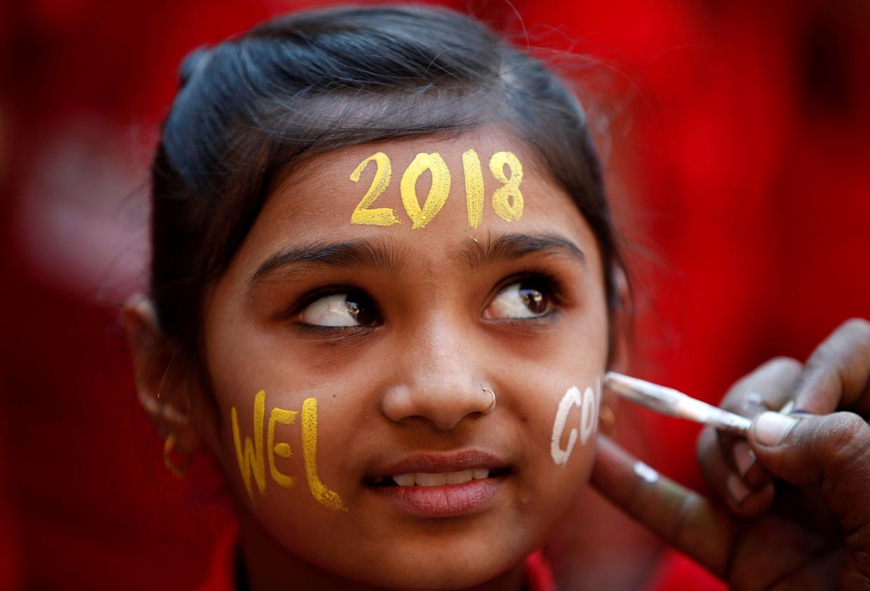 A schoolgirl reacts as she gets her face painted during New Year's celebrations at her school in Ahmedabad, India. (Photo: Amit Dave / Reuters)