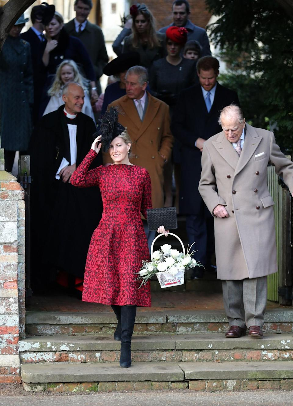 <p>Looking festive in red holding a contrasting pair of white roses [Photo: PA] </p>