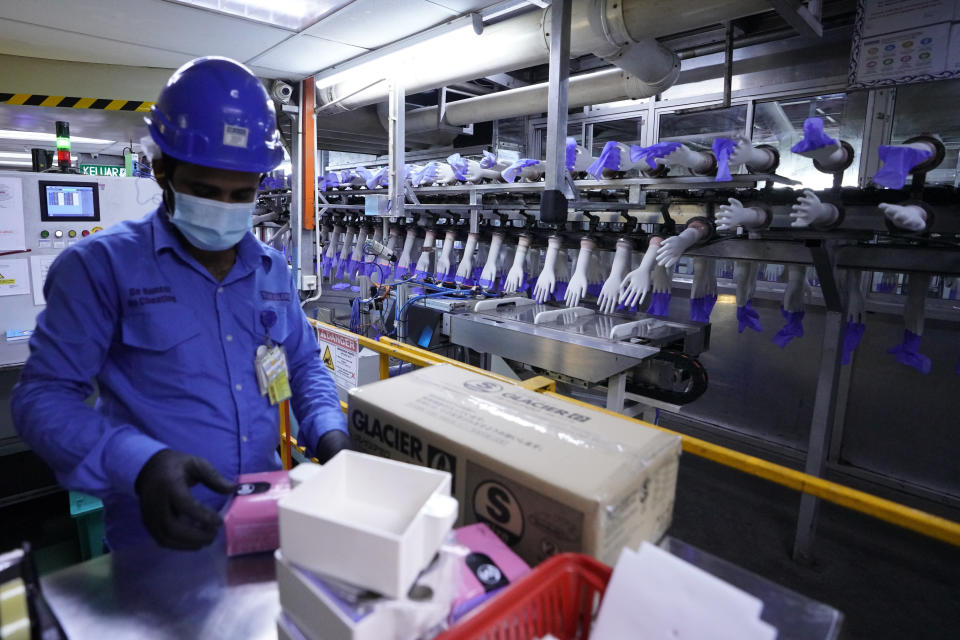 In this file picture taken Wednesday, Aug. 26, 2020, a worker packs disposable gloves at the Top Glove factory in Shah Alam on the outskirts of Kuala Lumpur, Malaysia. Malaysia's Top Glove Corp., the world's largest rubber glove maker, said Tuesday it expects a delay in deliveries after it was hit by a coronavirus outbreak that affected thousands of workers. (AP Photo/Vincent Thian)