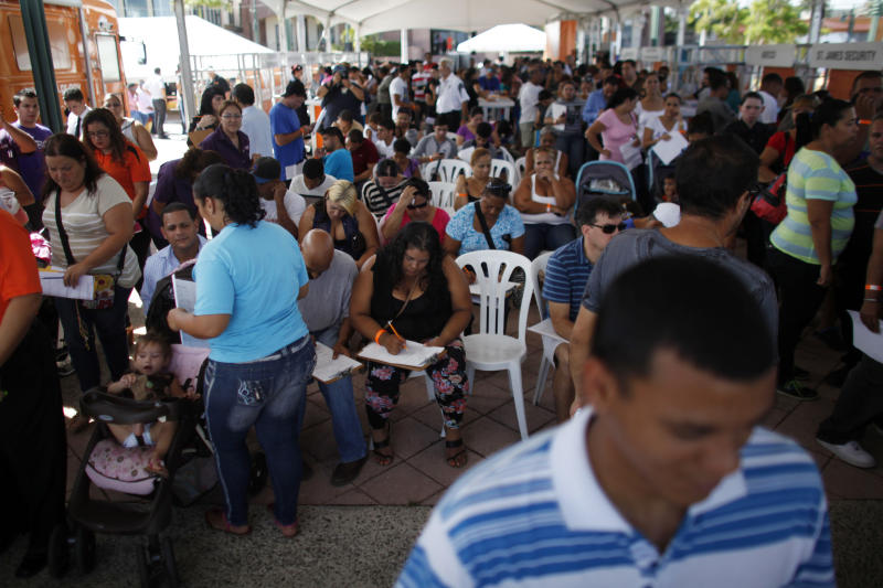 In this Sept. 25, 2013 photo, people gather at a job fair in Catano, Puerto Rico. Life in Puerto Rico was already expensive, and many middle class Puerto Ricans were barely making ends meet when the island was hit by a new business tax, more expensive gasoline and steep increases in the cost of water and sewer services, pushing many over the financial edge. (AP Photo/Ricardo Arduengo)