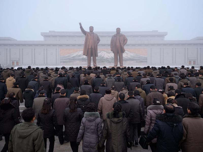 Pyongyang residents prepare to bow before statues of Kim Il Sung and Kim Jong Il during National Memorial Day on Sunday: AFP/Getty Images
